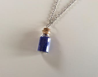 Necklace with its jar full of micro electric blue beads