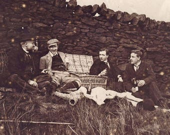 Young men enjoying a champagne picnic - Vintage photograph c1900s.