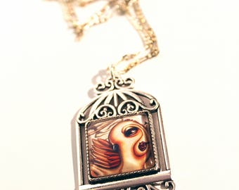 Birdcage necklace pendant with print of owl inside. Art by Susann Brox Nilsen. Silver or bronze colored. Illustration, owl, big eyes.
