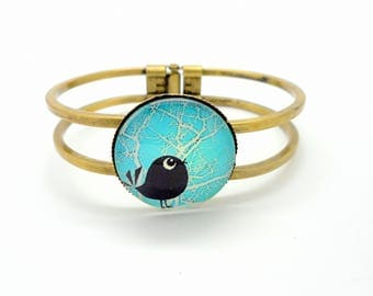 Fancy bracelet stiff bronze, bird charms and co. turquoise background
