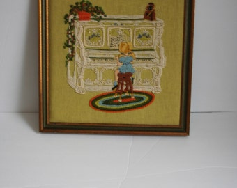 Vintage , boho style, Framed Needlework, girl at piano with plant and rug.