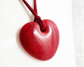 Red glass pendant, cast glass bright red on faux suede.