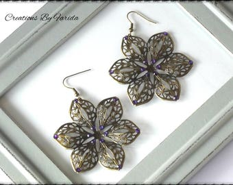 Bronze earrings dangle a flower with 6 petals with purple rhinestones