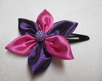 A pink and purple satin flower hair clip