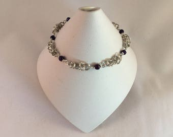 Chainmail bracelet. The weave is a Byzantine chainmail weave with small blue faceted  beads in between the weave.