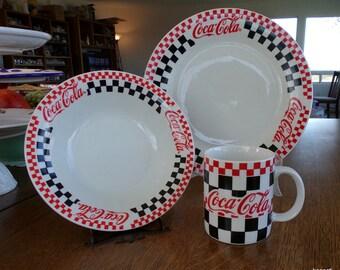"Gibson Coca-Cola red & black checks dinnerware set. 10 1/4"" Dinner plate, 8"" coupe soup bowl and 10oz mug. Coke logo and checkerboard design"