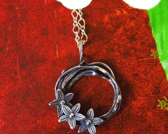 Hand made silver pendant of organic circle and little flowers