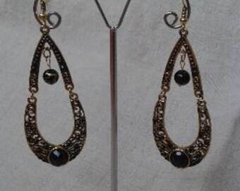 golden earrings and black rhinestones