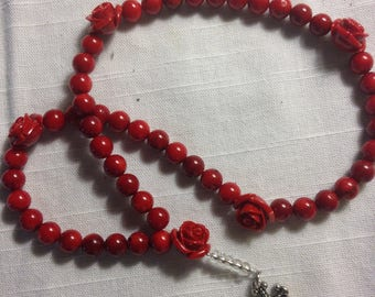These red glass beads and rose accents will delight anyone