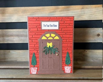 For Your New Home Card, Die Cut Front Door with Wreath Embellishment and Topiary Trees on Each Side, Embossed Brick Background