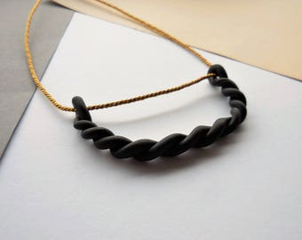 Handmade black modern minimalistic necklace of twisted claywith golden cord