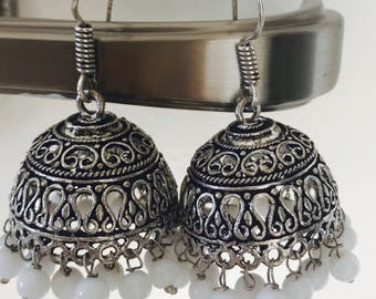 A round antique silver and white earring called jhumki also