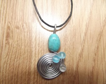 Pendant in aluminum with glass beads.