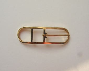 Oval belt buckle, 64 x 21 mm, gold tone.