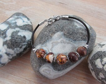 """Bracelet in warm colors on his """"Humus"""" leather cord"""