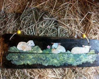 3 cute little sheep lying in grass painted on wood