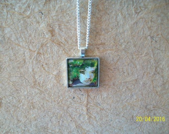 silver color square pendant and a glass cabochon