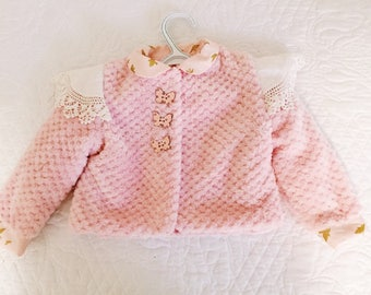 Peach minky baby jacket with doily embellishments.