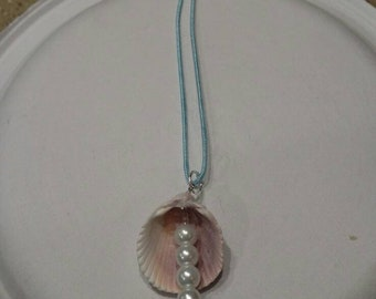 Pearl and seashell necklace with blue cord.