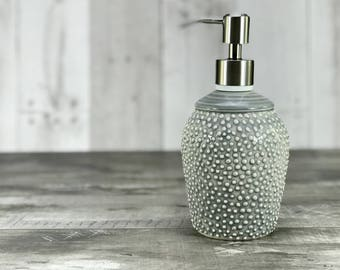 Grey soap dispenser. Porcelain soap dispenser. Ceramic soap dispenser. Grey bathroom. Gray bathroom. Textured pattern. Brushed nickel pump.