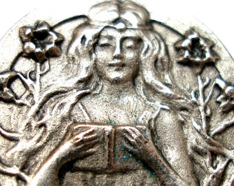 "Art Nouveau style button. Lady reading, in silver metal. 1""."