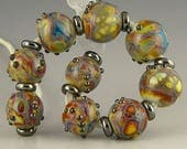 handmade lampwork glass beads a set of 9 rounds in white purple yellow red green blue marbled pattern - Raging Marble