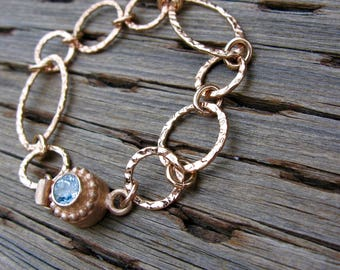 Rose gold bracelet with blue topaz clasp