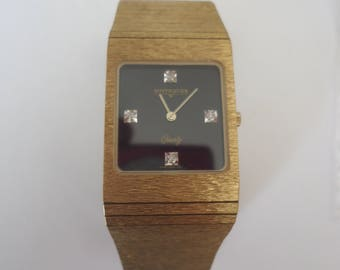 Circa 1980s Unisex Gold Tone Diamond Accent Longines Wittnauer Wrist Watch, Black Face, Fold Over Clasp, Extra Links Included