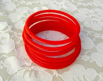 7 Stackable Bangle Bracelets in 3 shades of red, vintage lucite
