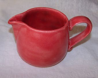 Cheerful bright red Cream or milk pitcher