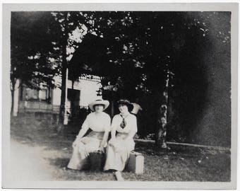 Old Photo 2 Women each Sitting on Suitcases wearing Long Skirts Hats outside Soft Focus 1910s Photograph Snapshot vintage