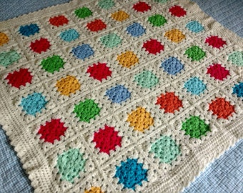 Hand made crocheted baby blanket featuring bright coloured granny squares on a cream background 88cm/35inches square
