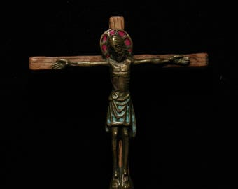 Antique wall hanging religious bronze and enamel crucifix on a wooden cross