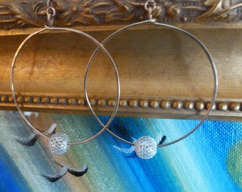 Gold And Silver Slider Hoops are simple, lightly hammered 2 inch gold hoops with sterling silver mesh balls sliding around. Light and lovely