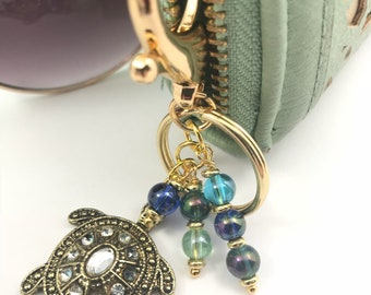 Gold keychain with turtle enlayed crystals, with blue and green tone glass beads.