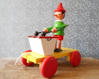 Vintage Pinocchio figurine pull toy, playing xylophon. French vintage wooden toy. Pinocchio trolley 70s.