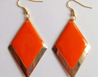 Dangle earrings with coral enamel lozenge and gilded edges.