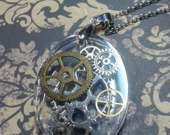 Metal necklace with resin pendant and gears. Steampunk style.