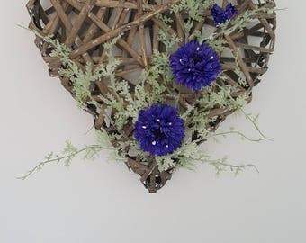 floral wall art, silk on a grey wicker heart.