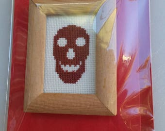 Red skull cross-stitch in a wooden frame on a card