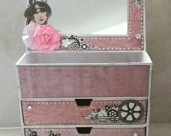 Small cabinet with drawers with mirror wrecked in pink in a shabby chic and steampunk style