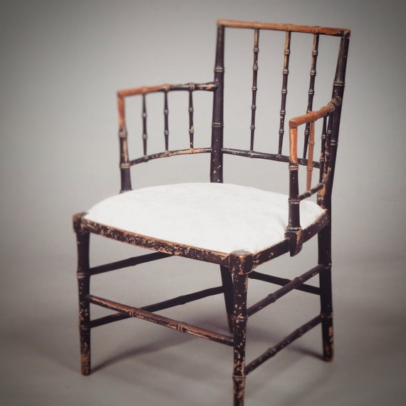 An early 19th century Sussex Morris style ebonised faux bamboo carved ash armchair with upholstered seat.