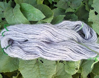 100% Alpaca Handspun Yarn 2 ply in very pale lavender/gray.  Worsted weight (11 wpi), aprox 87 yards/ 3.4 ounces