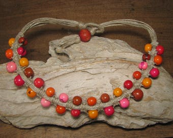 Short necklace with Acai seeds in red, orange and pink woven in a linen macramé