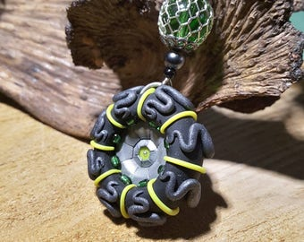 Black, silver and neon yellow round pendant with metal pieces and beads. Hand sculpted pendant.