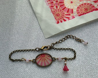 Bracelet, pink and white geometric patterned paper.