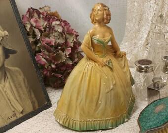 A vintage chalkware figure of lady in a crinoline dress.