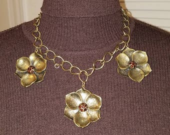 Bold antique gold statement piece adorned with 3 flower accented with centered decorative stones