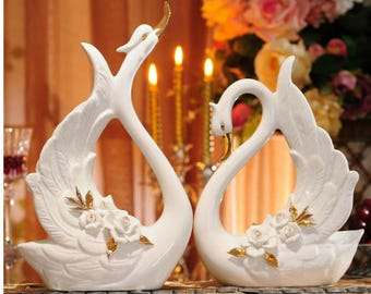 Pair of Porcelain Swans with an Arrangement of White Pinched Roses