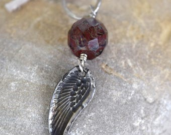Angel Wing pendant with garnet colored glass jewel. Stone and glass beads with fine silver accents
